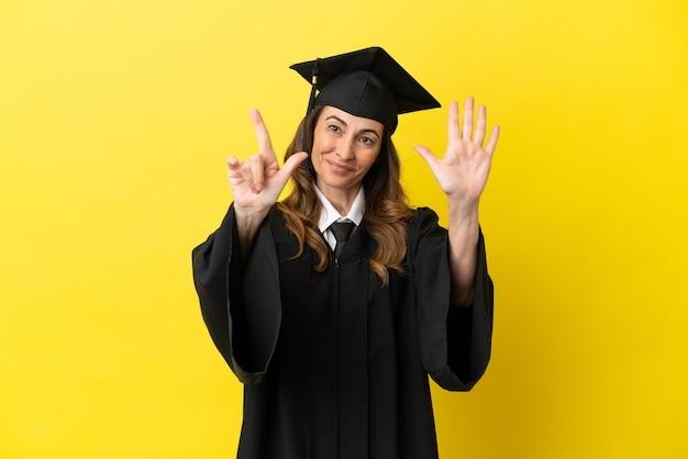 노란색 배경에 격리된 중년 대학 졸업생은 손가락으로 7을 세고 있습니다.