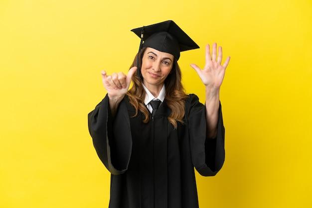 노란색 배경에 격리된 중년 대학 졸업생은 손가락으로 6을 세고 있습니다.
