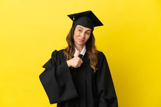 親指を立てるジェスチャーを与える黄色の背景に分離された中年の大学卒業生