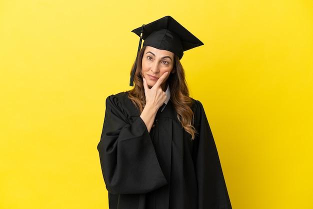 Выпускник университета среднего возраста изолирован на желтом фоне с сомнениями и смущенным выражением лица