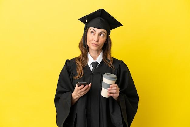 노란색 배경에 격리된 중년의 대학 졸업생은 커피를 들고 무언가를 생각하는 동안 휴대전화를 들고 있습니다.