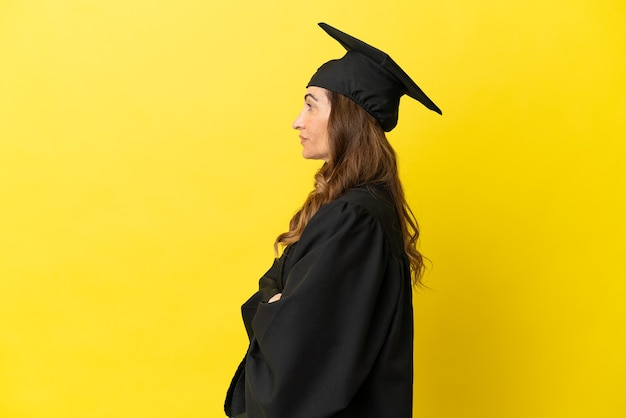 측면 위치에 노란색 배경에 고립 된 중년 대학 졸업