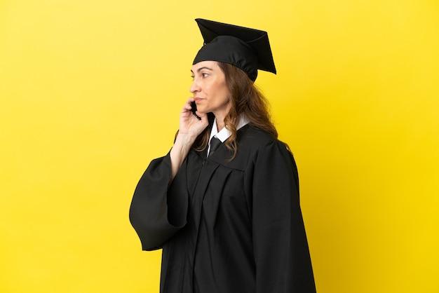 Выпускник университета средних лет изолирован на желтом фоне и разговаривает с кем-то по мобильному телефону