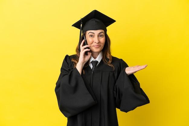 노란색 배경에 격리된 중년의 대학 졸업생은 누군가와 휴대폰으로 대화를 나눴습니다.