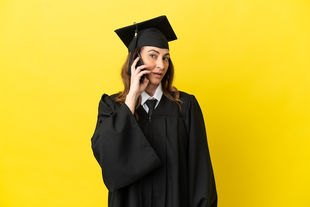 휴대 전화와 대화를 유지 하는 노란색 배경에 고립 된 중 년 대학 졸업