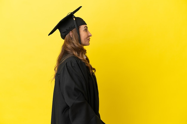 노란색 배경에 고립 된 중년 대학 졸업생은 옆 위치에서 웃고 있습니다.