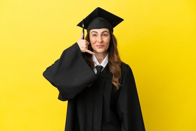 Выпускник университета среднего возраста, изолированные на желтом фоне, делая телефонный жест. перезвони мне знак