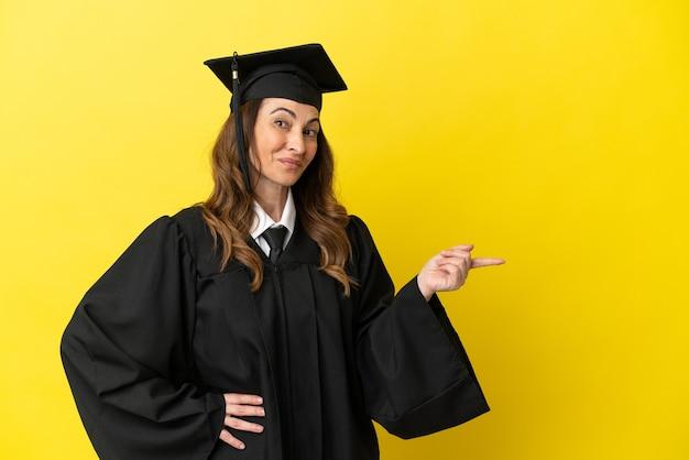 노란색 배경에 고립 된 중년 대학 졸업생은 손가락을 옆으로 가리키고 제품을 제시합니다.