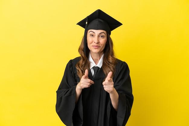 노란색 배경에 고립되어 앞을 가리키고 웃고 있는 중년의 대학 졸업