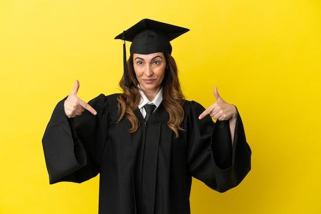 Выпускник университета среднего возраста изолирован на желтом фоне, гордый и самодовольный