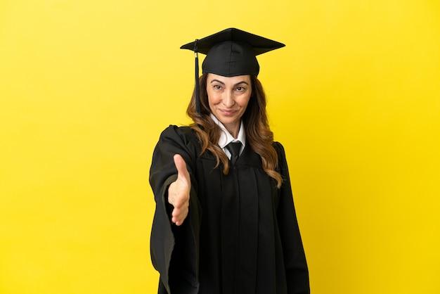 Выпускник университета среднего возраста изолирован на желтом фоне, пожимая руку для заключения хорошей сделки