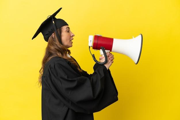 확성기를 통해 외치는 노란색 배경에 고립 된 중년 대학 졸업생