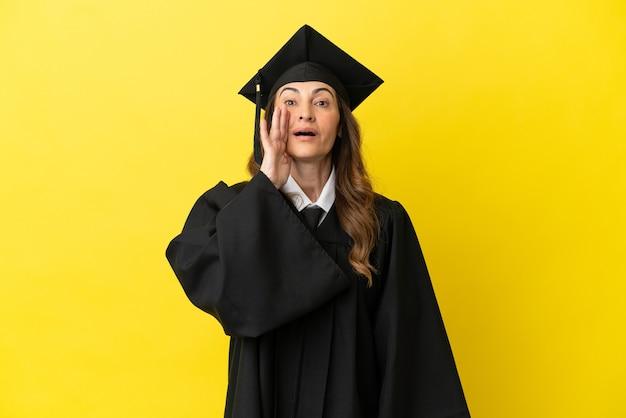 口を大きく開いて叫んで黄色の背景に分離された中年の大学卒業生