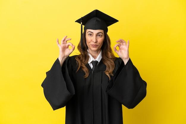노란색 배경에 고립되어 손가락으로 확인 표시를 하는 중년 대학 졸업