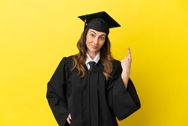 Выпускник университета средних лет изолирован на желтом фоне, показывая и поднимая палец в знак лучших