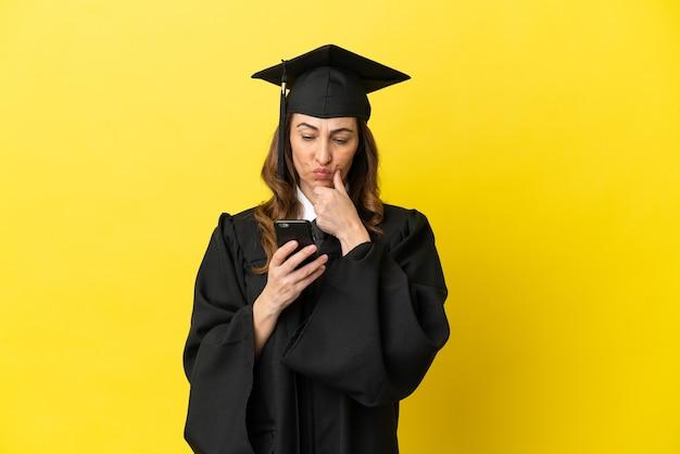 Выпускник университета среднего возраста изолирован на желтом фоне, думая и отправляя сообщение