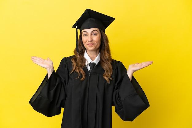 놀란 표정으로 노란색 배경에 고립 된 중년 대학 졸업생