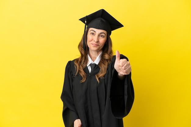 좋은 일이 일어났기 때문에 엄지손가락으로 노란색 배경에 고립된 중년 대학 졸업