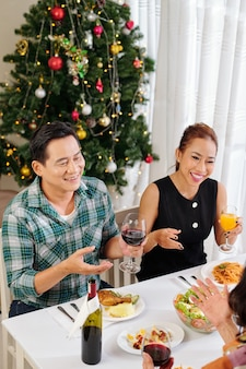 家でクリスマスディナーをするときに友達に面白い話をする中年のベトナム人カップル