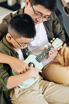 Middle-aged vietnamese man teaching preteen son how to play ukulele