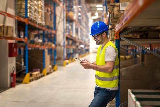 Складской рабочий среднего возраста с каской с помощью планшета на большой складской площади