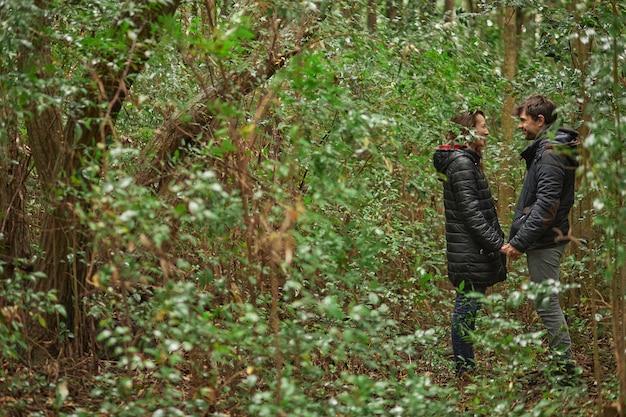 Свадебная пара средних лет, взявшись за руки и глядя друг другу в глаза в лесу. зимой они носят пальто. кавказцы.