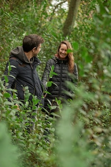 Middle-aged wedding couple holding hands and looking into each other's eyes in the forest. they wear a coat in winter. caucasians.