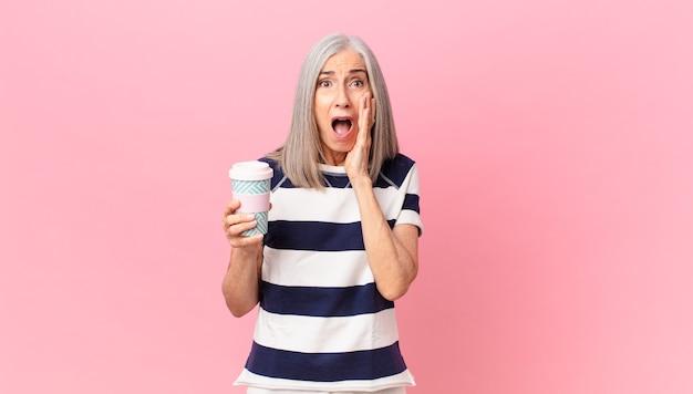 Женщина средних лет с белыми волосами чувствует себя шокированной и напуганной и держит контейнер для кофе на вынос
