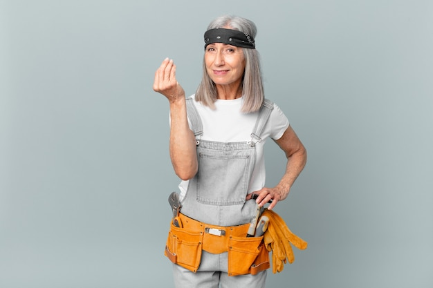 Middle aged white hair woman making capice or money gesture, telling you to pay and wearing work wear and tools