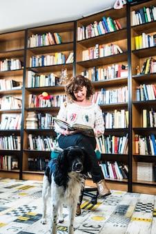 중간 세 여자와 그녀의 강아지는 그녀의 도서관에서 책을 읽고