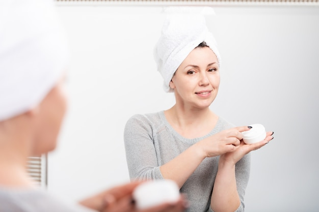Middle aged woman applying anti-aging cream before mirror at home
