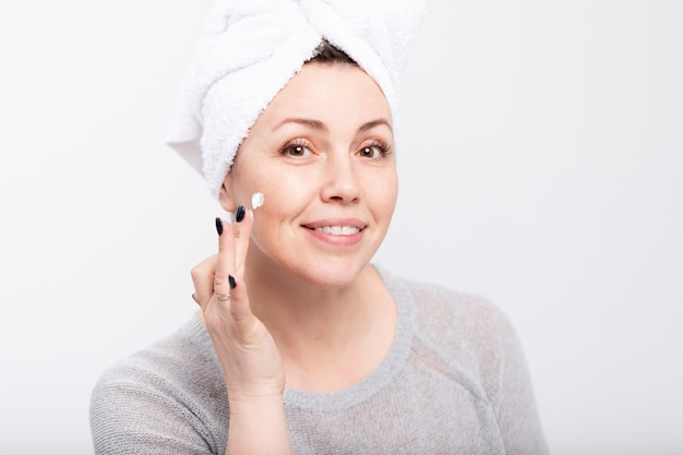 Middle aged woman applying anti-aging cream before mirror