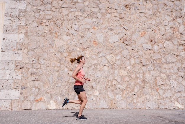 Middle aged woman athlete with fitness clothes doing exercises and running in the sun and sweating
