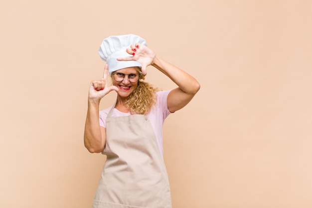 幸せで、フレンドリーで、前向きで、笑顔で、手でポートレートやフォトフレームを作る中年女性のパン屋