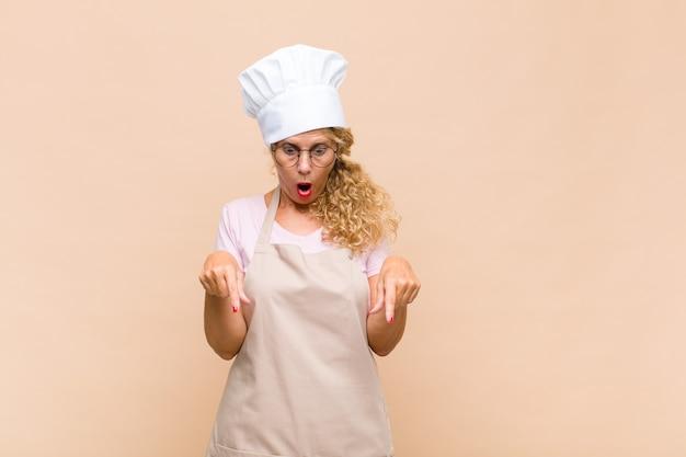 Женщина-пекарь средних лет чувствует себя потрясенной, с открытым ртом и изумлением, глядя и указывая вниз в недоумении и удивлении
