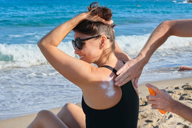 Middle-aged woman on the beach, male hands applying sun-shaped cream