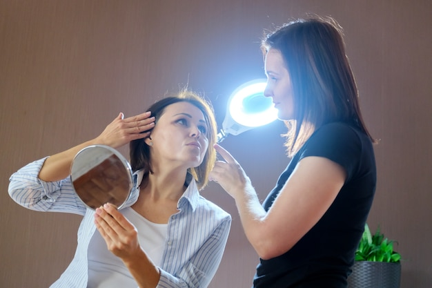 Middle-aged woman in beauty salon, female talking to a beautician