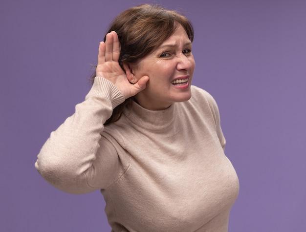 Donna di mezza età in dolcevita beige tenendo la mano sull'orecchio cercando di ascoltare i pettegolezzi in piedi sul muro viola