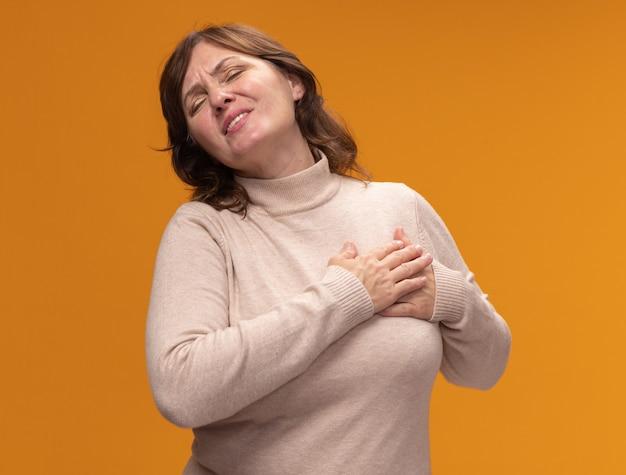 Donna di mezza età in dolcevita beige che tiene la mano sul petto sentendosi grata con gli occhi chiusi in piedi sopra il muro arancione