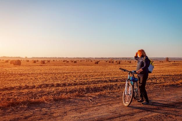 日没時に秋の畑に乗って中年女性の自転車に乗る人。眺めを賞賛するシニアスポーツウーマン。