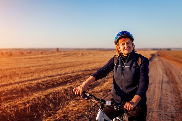 日没時に秋の畑に乗って中年女性の自転車に乗る人。趣味を楽しむシニアスポーツウーマン。健康的な生活様式