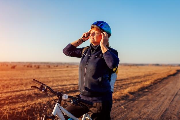 中年女性の自転車に乗る人が日没時に秋のフィールドでヘルメットを着用して固定します。趣味を楽しむシニアスポーツウーマン。