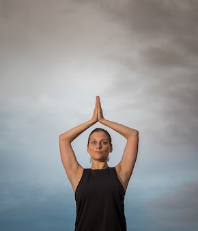Middle aged woman in black tank top with her arms over her head doing meditation outdoors with cloudy sky