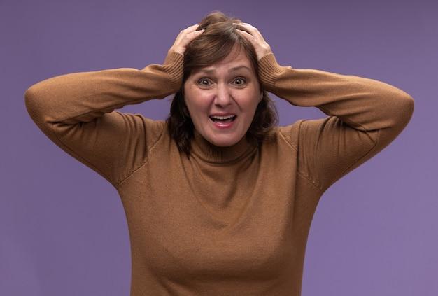Donna di mezza età in dolcevita marrone confusa con le mani sulla testa per errore in piedi sul muro viola
