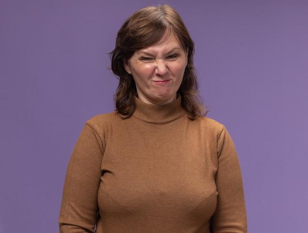 Donna di mezza età in dolcevita marrone che fa smorfia infelice e scontenta in piedi sopra il muro viola
