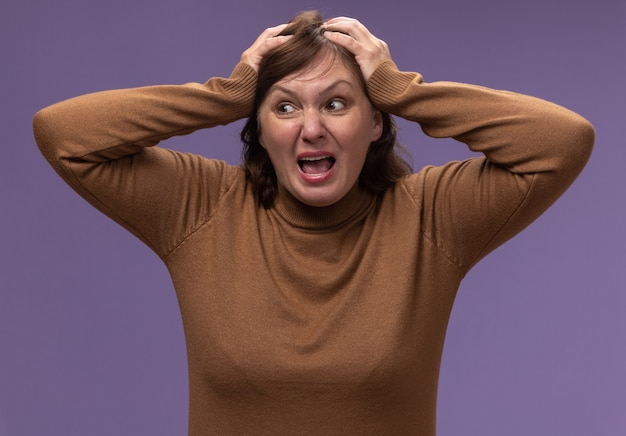 Donna di mezza età in dolcevita marrone che grida impazzendo tirando i capelli in piedi sopra il muro viola