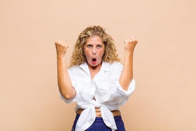 Женщина средних лет празднует невероятный успех как победительница, выглядит взволнованной и счастливой и говорит: «бери!»