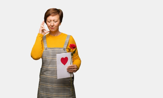 Middle aged woman celebrating valentines day crossing fingers for having luck