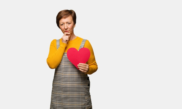 Middle aged woman celebrating valentines day doubting and confused