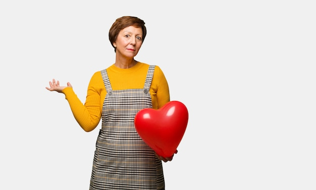 Middle aged woman celebrating valentines day doubting and shrugging shoulders